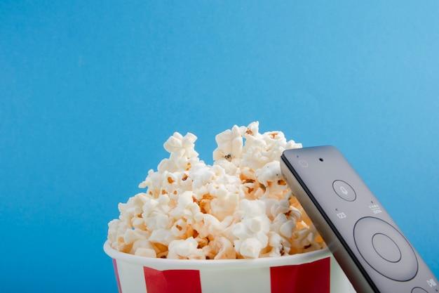 Kubek papierowy w paski z popcornem, pilot do telewizora