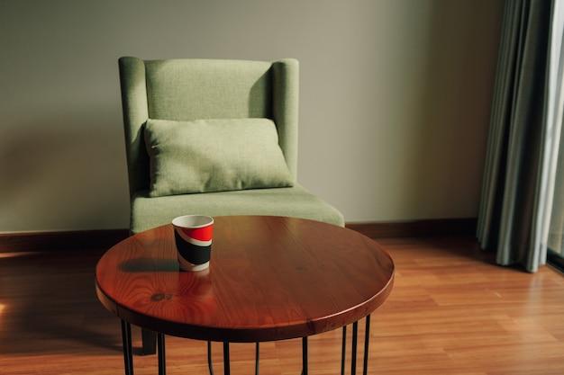 Kubek papierowy z gorącym napojem na stole z zielonym krzesłem w klasycznym przytulnym barze.