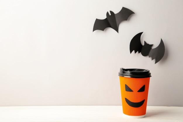 Kubek papierowy z halloweenową twarzą na szarej powierzchni z halloweenowymi nietoperzami