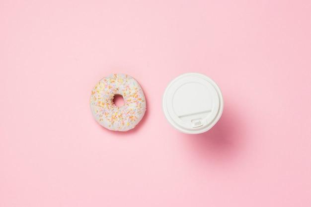 Kubek papierowy z kawą lub herbatą. świeży smakowity słodki pączek na różowym tle. koncepcja piekarni, świeże wypieki, pyszne śniadanie, fast food, kawiarnia. leżał płasko, widok z góry.
