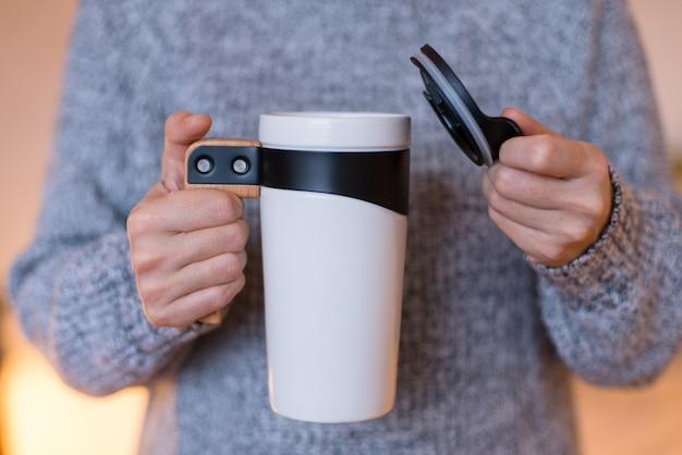 Kubek podróżny z termosem, biały kubek, kubek do herbaty lub kawy w rękach kobiety
