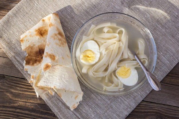 Kubek rosołu z makaronem i jajkami i chlebkiem pita