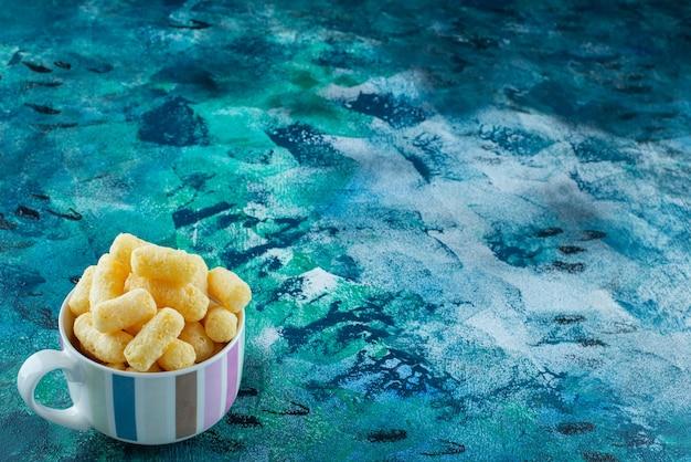 Kubek słodkich paluszków kukurydzianych na niebieskim stole.