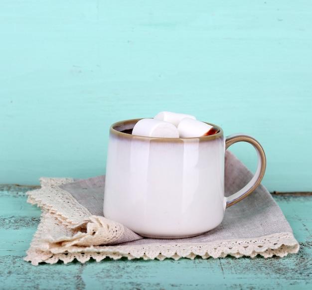 Kubek smacznego gorącego kakao, na drewnianym stole, na kolorowym tle