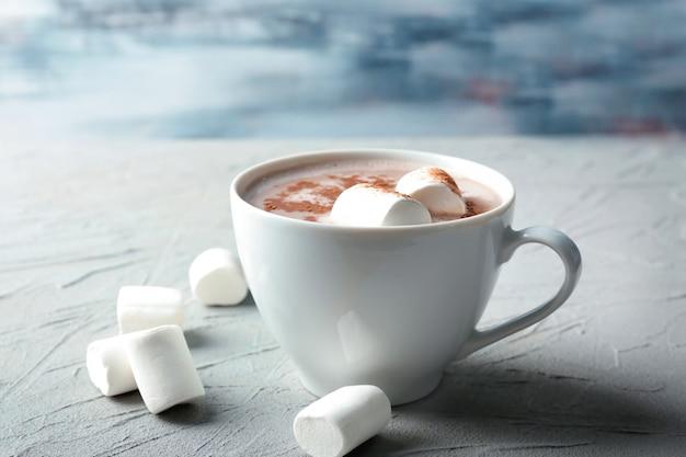 Kubek smacznego napoju kakaowego z pianką marshmallow na stole z teksturą