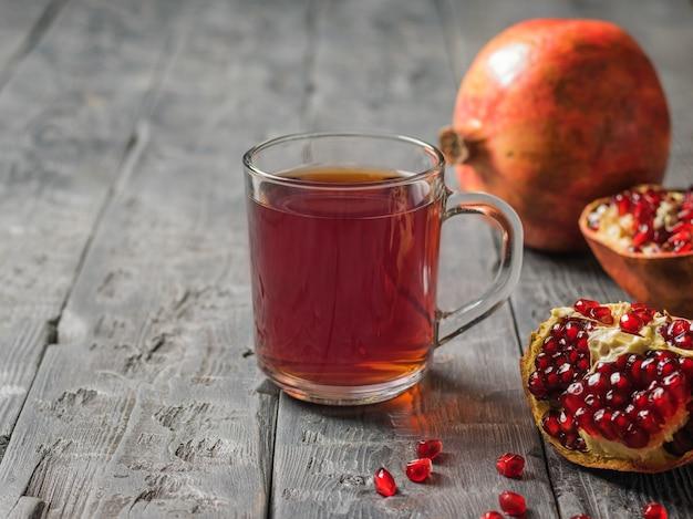 Kubek soku z granatów i połamane granaty na drewnianym stole. napój przydatny dla zdrowia.