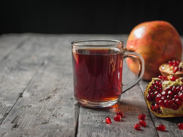 Kubek soku z granatów i połamane granaty na rustykalnym stole. napój przydatny dla zdrowia.