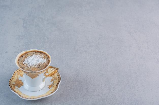 Kubek spienionej gorącej kawy umieszczony na tle kamienia.