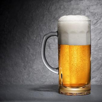Kubek świeżego piwa z pianką na czarnym tle łupków