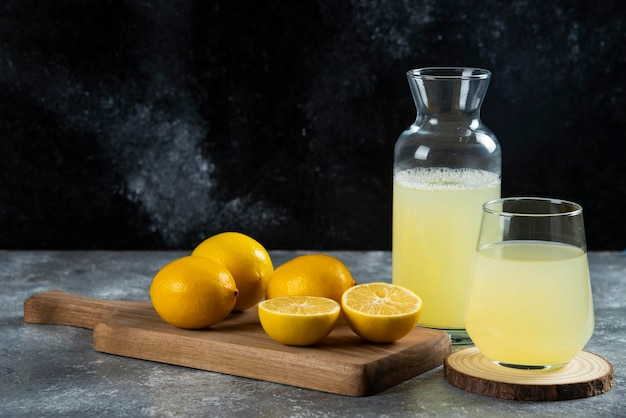 Kubek świeżego soku z cytryny na desce.