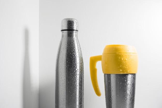 Kubek termiczny ze stali w kolorze żółtym i termos ze stali ekologicznej spryskany wodą na białym tle.