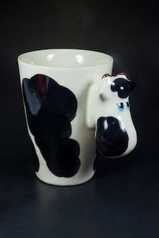 Kubek w kształcie krowy, czarne tło, zbliżenie.