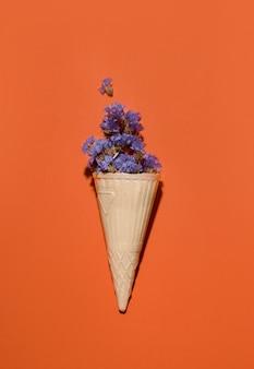 Kubek waflowy z fioletowymi kwiatami na pomarańczowej przestrzeni. skopiuj miejsce.