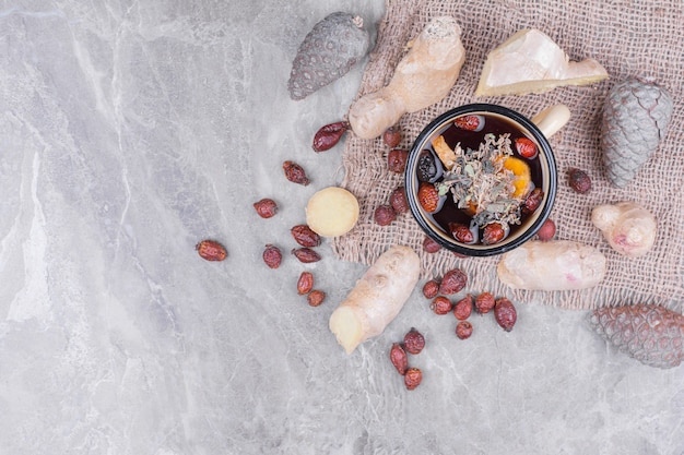 Kubek wina błyszczącego z suszonymi biodrami i plasterkami imbiru