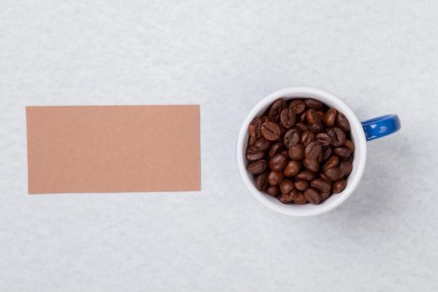 Kubek wypełniony ziarnami kawy i czystym papierem na copyspace