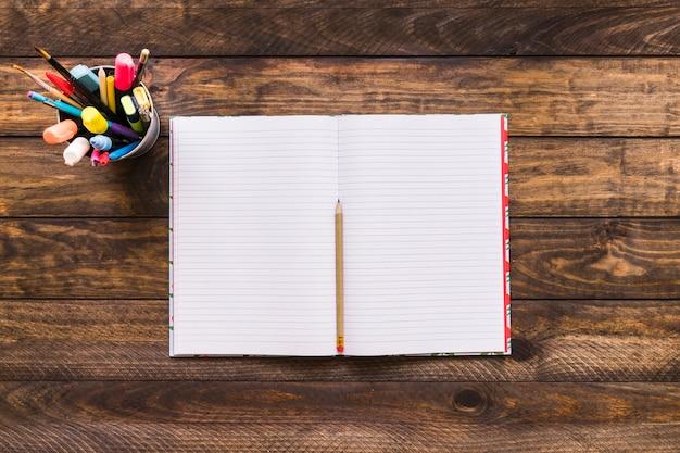 Kubek z artykułami do pisania w pobliżu notatnika