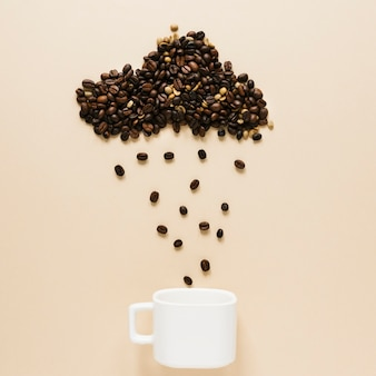 Kubek z chmurą ziaren kawy