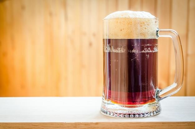 Kubek z ciemnym piwem na podłoże drewniane