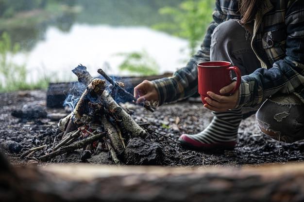 Kubek z ciepłym napojem podczas wędrówki po lesie przy ognisku.