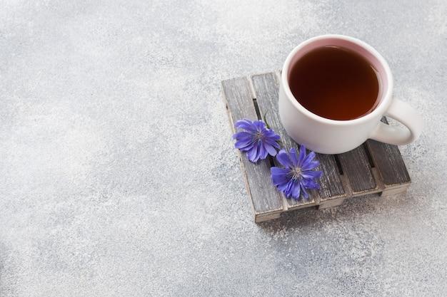 Kubek z cykorią i kwiatami niebieskiej cykorii na szarym stole