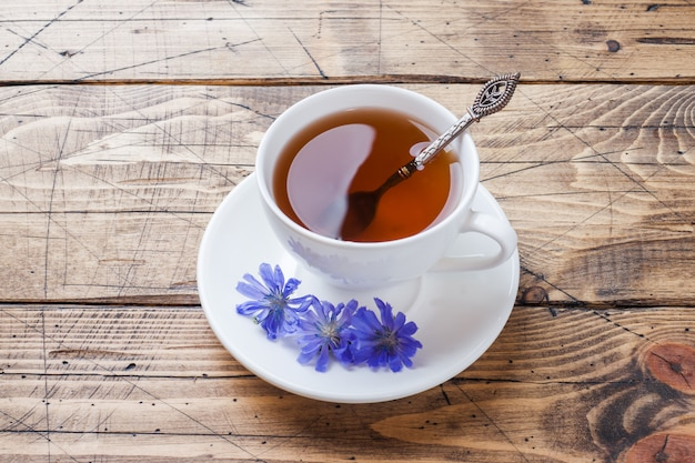 Kubek z cykorii pić i kwiaty cykorii niebieski na drewnianym stole