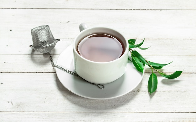 Kubek z czarną herbatą na białym drewnianym stole