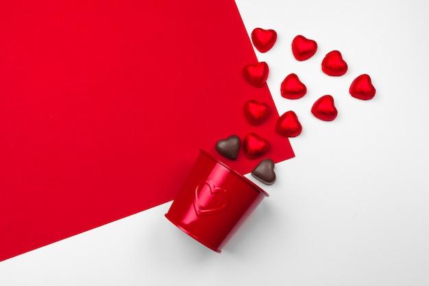 Kubek z czekoladowymi sercami na czerwonym tle. kompozycja płasko świecąca. romantyczna koncepcja na walentynki
