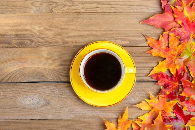 Kubek z gorącą czarną kawą na drewnianym stole z opadłymi jesienią żółtymi, pomarańczowymi i czerwonymi liśćmi