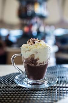 Kubek z gorącą czekoladą i bitą śmietaną w barze w restauracjach.