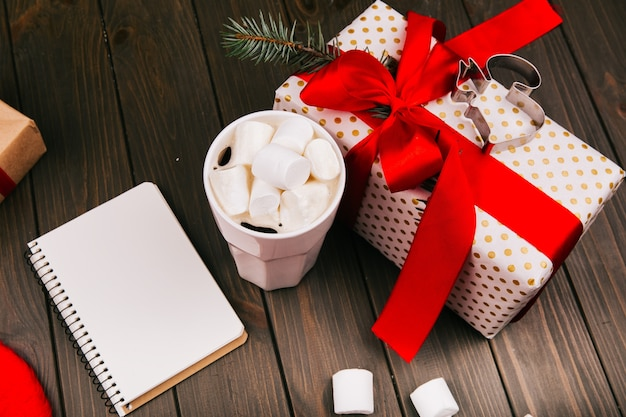 Kubek z gorącą czekoladą i marshmallows stoi na podłodze przed obecnym pudełku i pustym notatniku