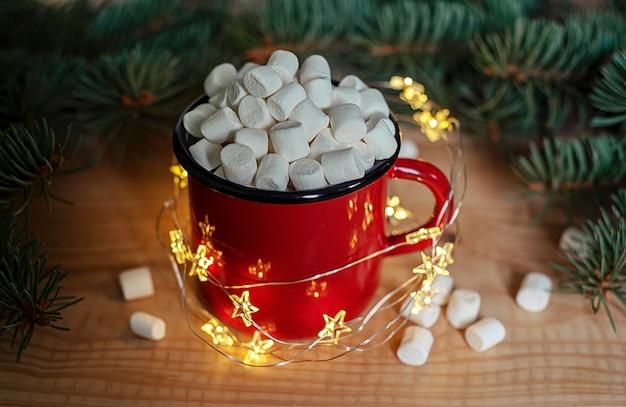 Kubek z gorącą czekoladą z piankami, lampkami choinkowymi i gałązkami choinki