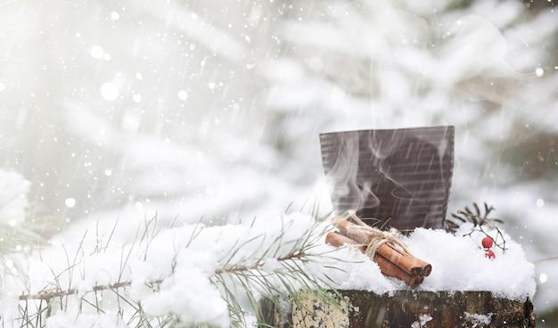 Kubek z gorącym napojem w zimowym lesie. gorące kakao z cynamonem na tle zimowego lasu. pierwszy śnieg i gorąca czekolada.