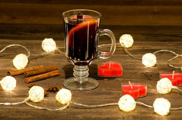 Kubek z grzanym winem z przyprawami, świeczki w kształcie serca na drewnianym stole, girlanda z lampionów.