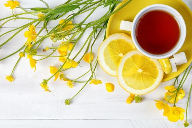 Kubek z herbatą i cytryną są na drewnianym stole.