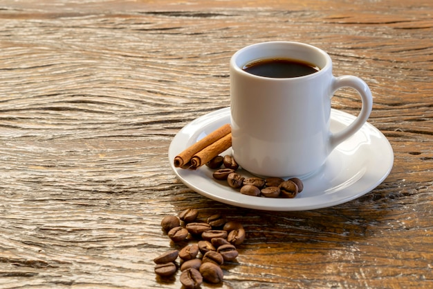 Kubek z kawą, cynamonem i ziarnami kawy na rustykalnym stole