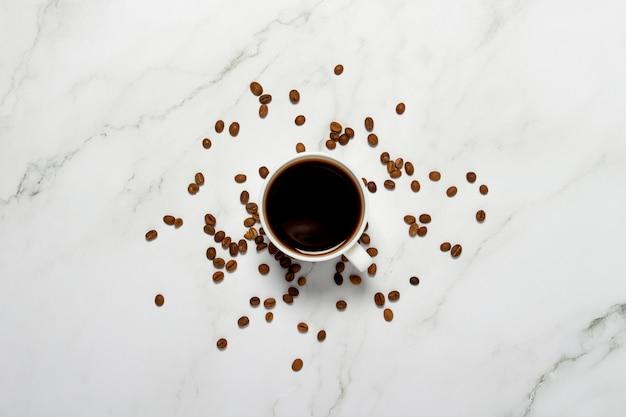 Kubek z kawą i ziarnami kawy na marmurowym stole. koncepcja śniadanie, czarna kawa, kawa na noc, bezsenność. widok płaski, widok z góry