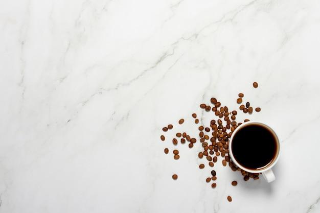 Kubek z kawą i ziarnami kawy na marmurowym stole. koncepcja śniadanie, czarna kawa, kawa na noc, bezsenność