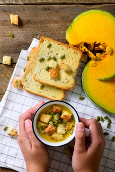 Kubek z marchewką zupa krem w rękach dziewczyny z nasionami, krakersy