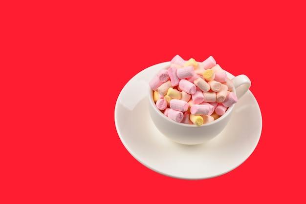Kubek z pianką marshmallow na czerwonej powierzchni
