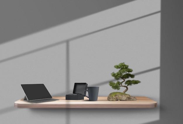 Kubek z pudełkiem na tablet i drzewko bonsai na drewnianej półce zawieszonej na szarych cieniach ściennych z ...