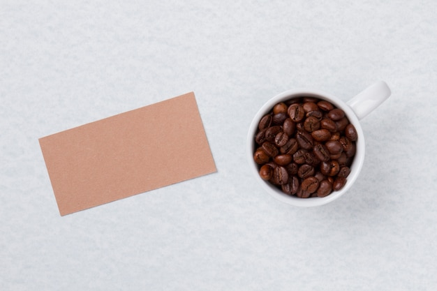 Kubek z widokiem z góry wypełniony ziarnami kawy i czystym papierem