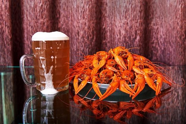 Kubek z zimnym piwem i gorącymi rakami gotowanymi.