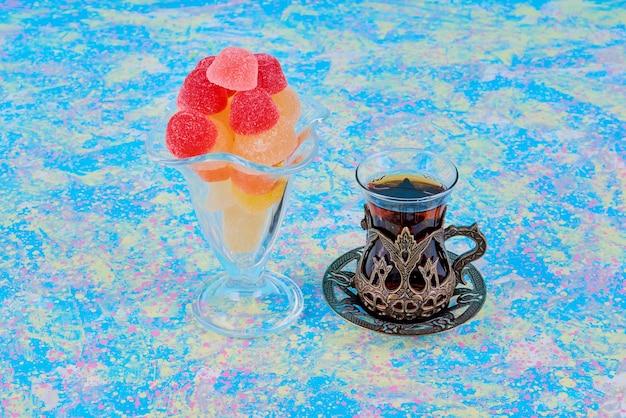 Kubek żelkowych cukierków podawany ze szklanką herbaty.