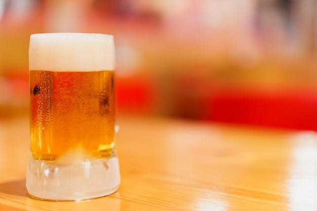 Kubek zimnego piwa z beczki na drewnianym stole