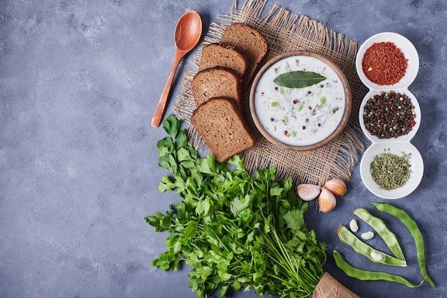 Kubek zupy jogurtowej podawany z kromkami chleba, ziołami i przyprawami.