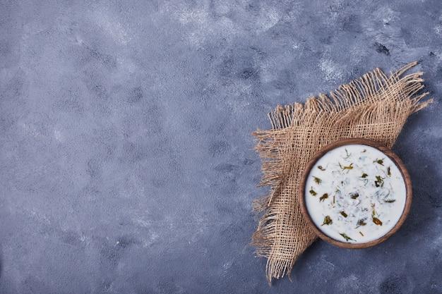 Kubek zupy jogurtowej z ziołami i przyprawami.