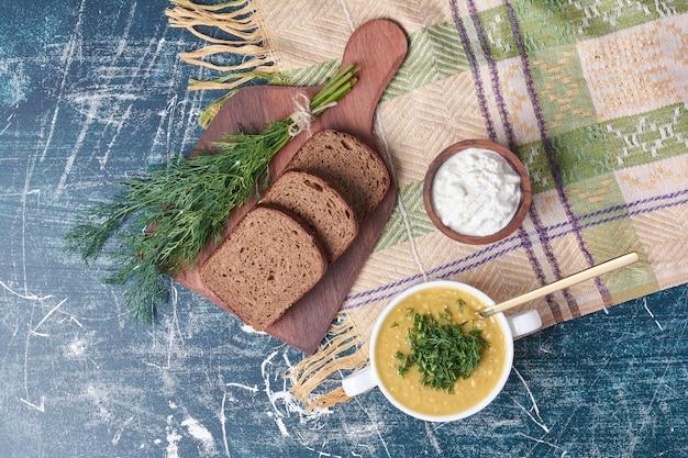 Kubek zupy z chlebem tostowym i jogurtem.