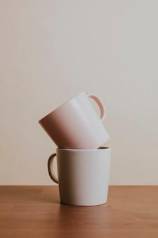 Kubki ceramiczne do kawy w kolorze ziemi na drewnianym stole