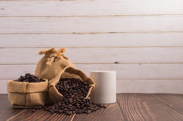 Kubki do kawy i ziarna kawy w workach na stole z ciemnego drewna i ścianie z jasnego drewna