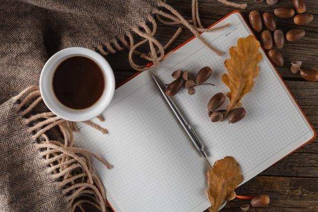 Kubki do kawy, notatnik i jesienne liście